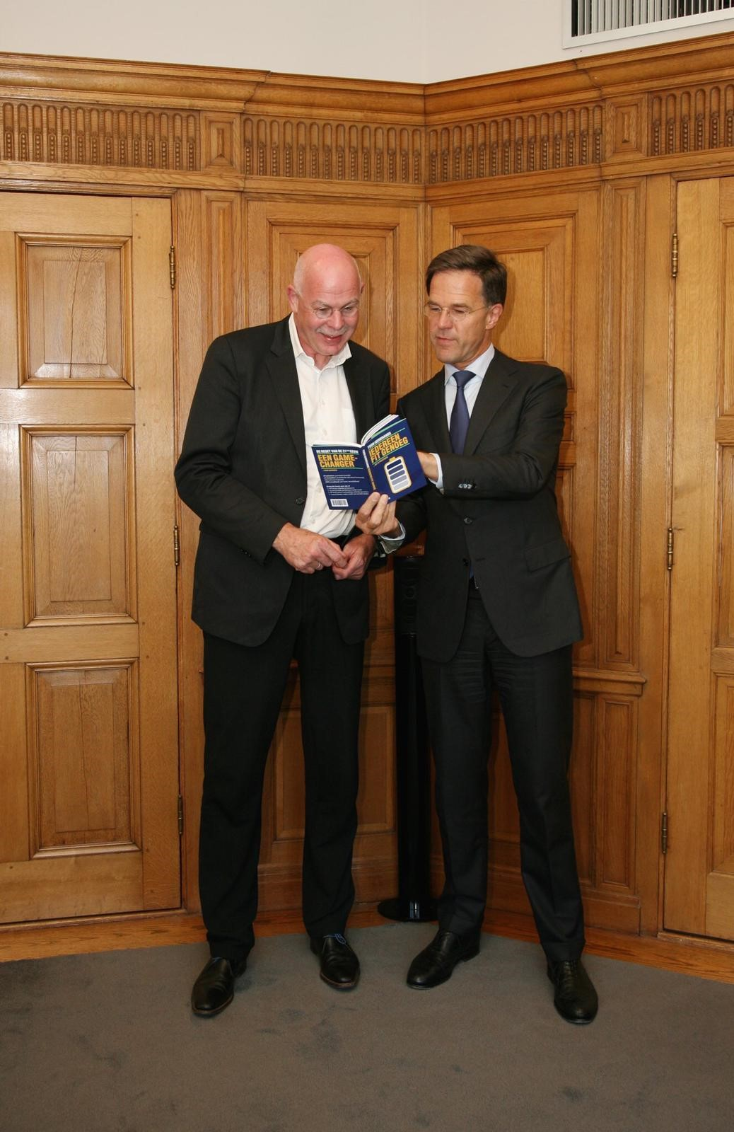 dit is een foto van Toon Gerbrands met Mark Rutte, waarin minister president mark rutte voorleest uit een vand eboeken van Toon gerbrands die directeur van PSV is. Samen eenvoudig vooruit blijven gaan.
