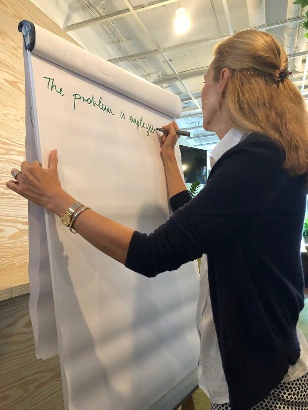een action learning deelnemer schrijft op een flipover de kern van het probleem. dit begint met de woorden: the problem is ... Samen eenvoudig vooruit blijven gaan..